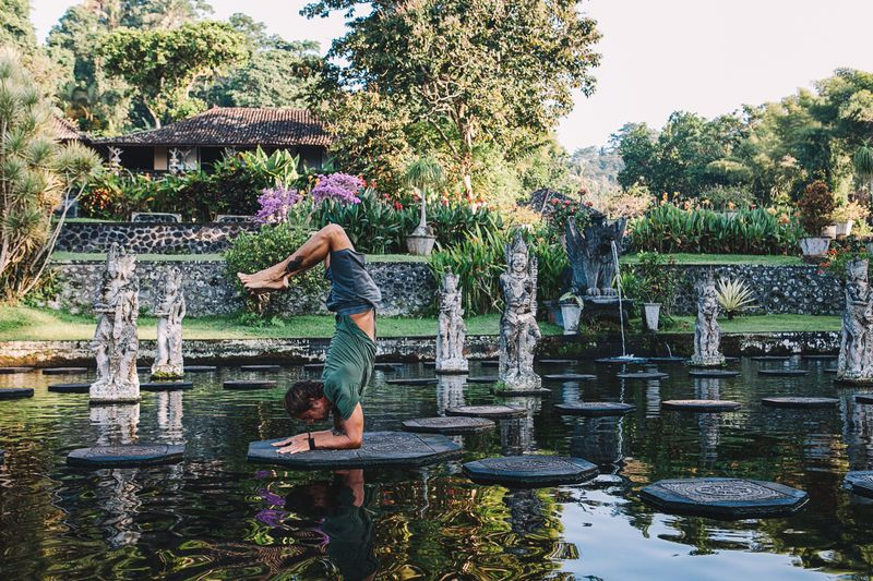 striking a yoga pose in bali, indonesia