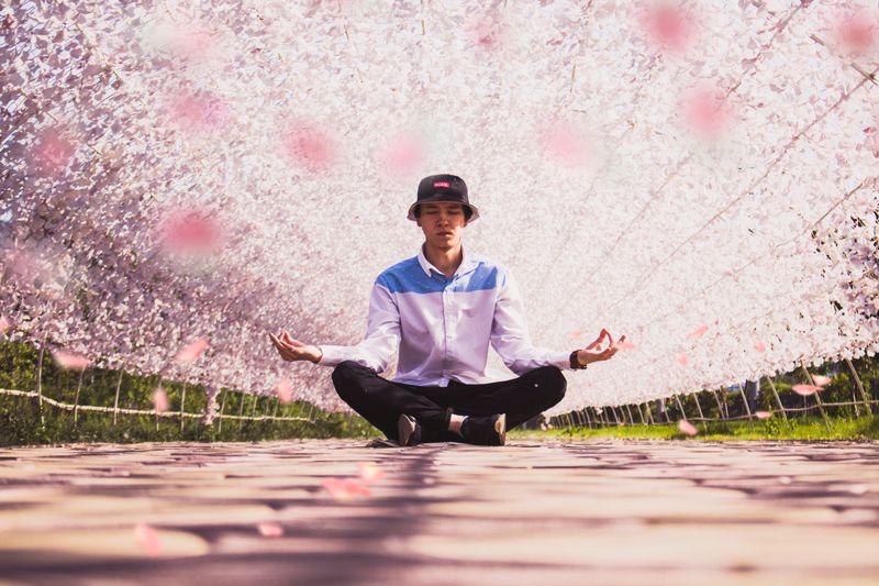 man meditating next to pink flower tree