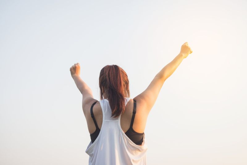 woman with hands in the air in fitness clothing