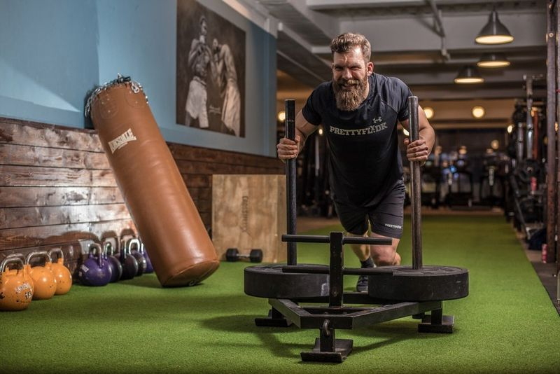 bearded man working out on a gym machine