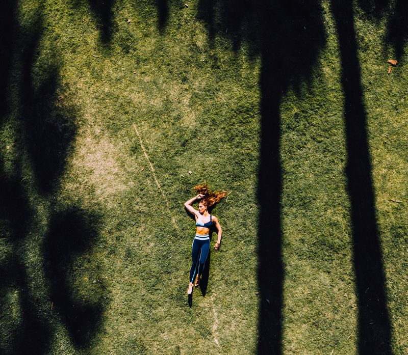 woman in sportive outfit lying on the grass
