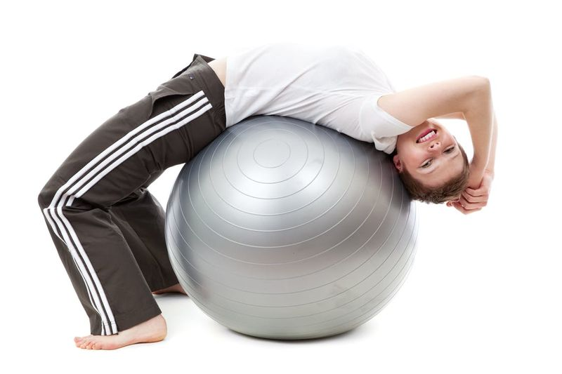 woman being active lying on her back on an activity ball