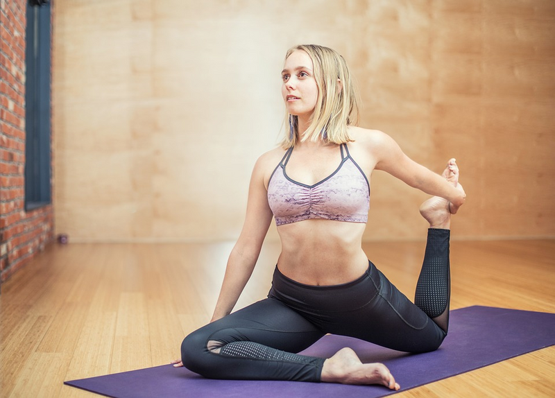 woman doing a stretch before yoga on the mat
