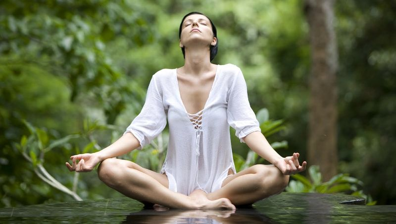 woman white shirt yoga pose middle of nature