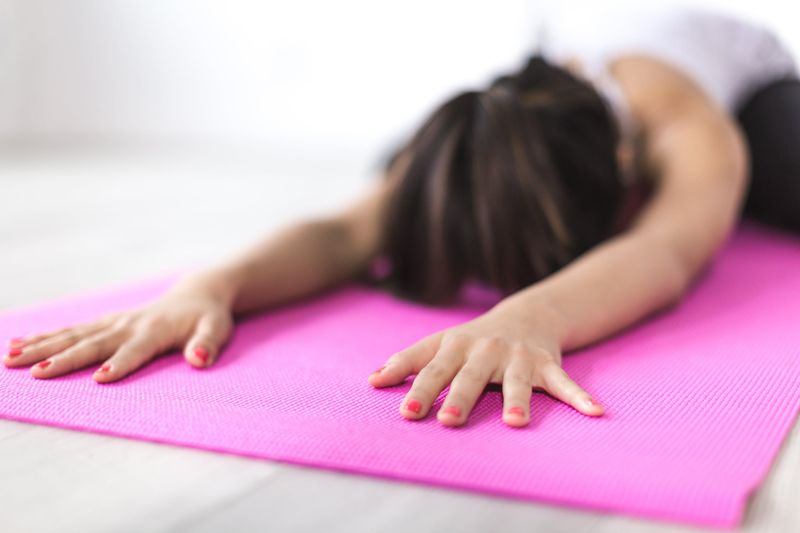 woman stretched with hands in front on yoga mat