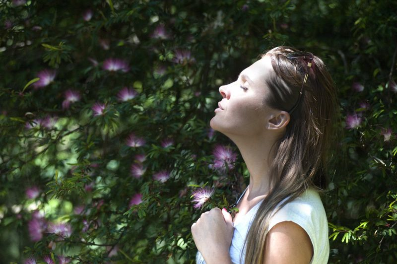 woman in middle of nature meditating pink flower bush