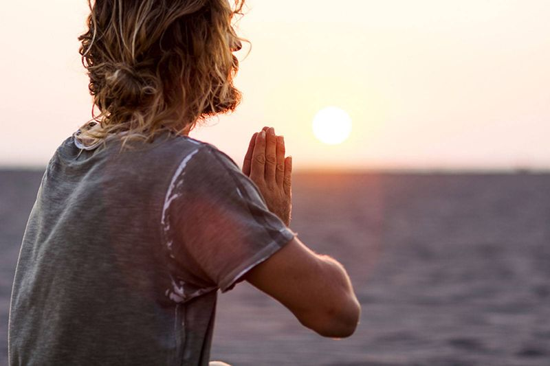 man practicing yoga in light of the sunset