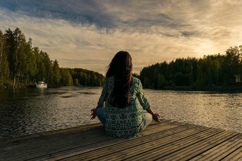 woman practicing meditation by the lake