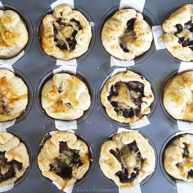 Mushroom, peas & guyere mini pies on a baking pan