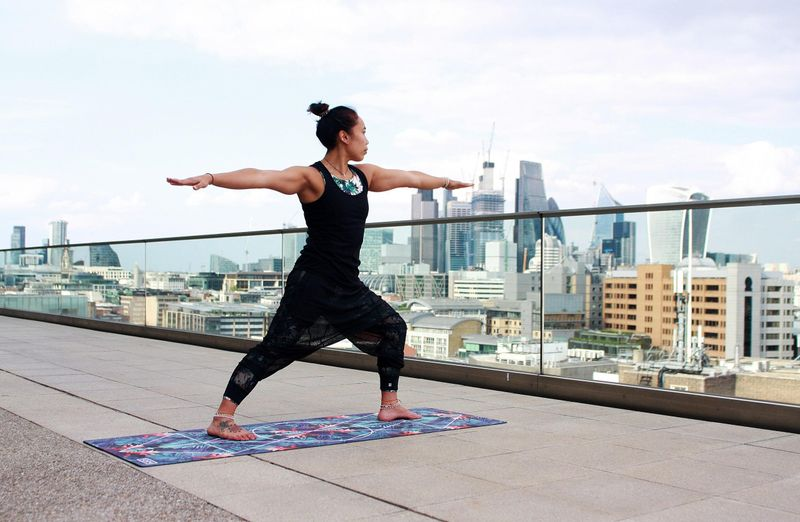 woman in back practicing yoga on the roof