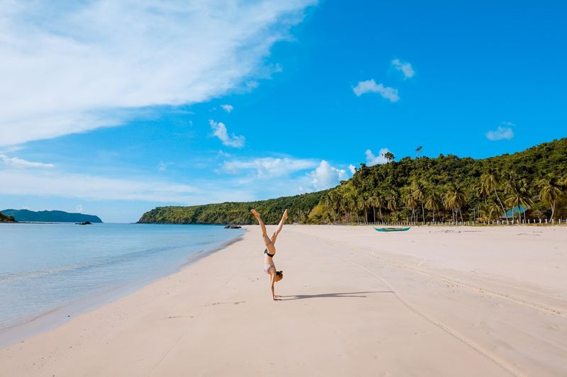 woman standing on her arms on the beach flexibility