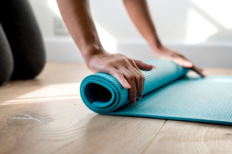 woman hands unrolling a yoga mat