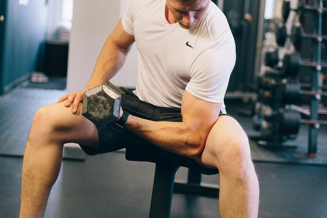 man showing off muscles biceps gym