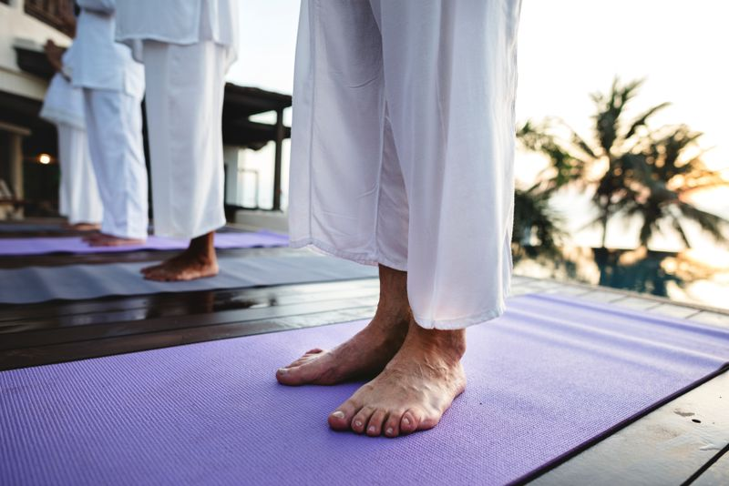 barefoot people standing on yoga mats