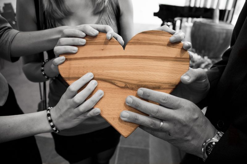 People holding wooden heart