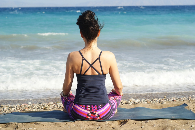 woman on the beach in lotus pose