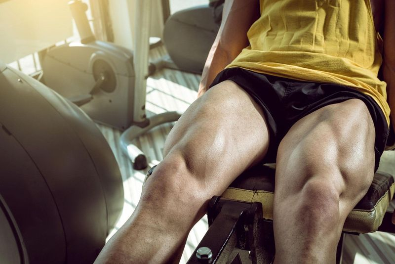 man sitting in gym muscles on legs close-up