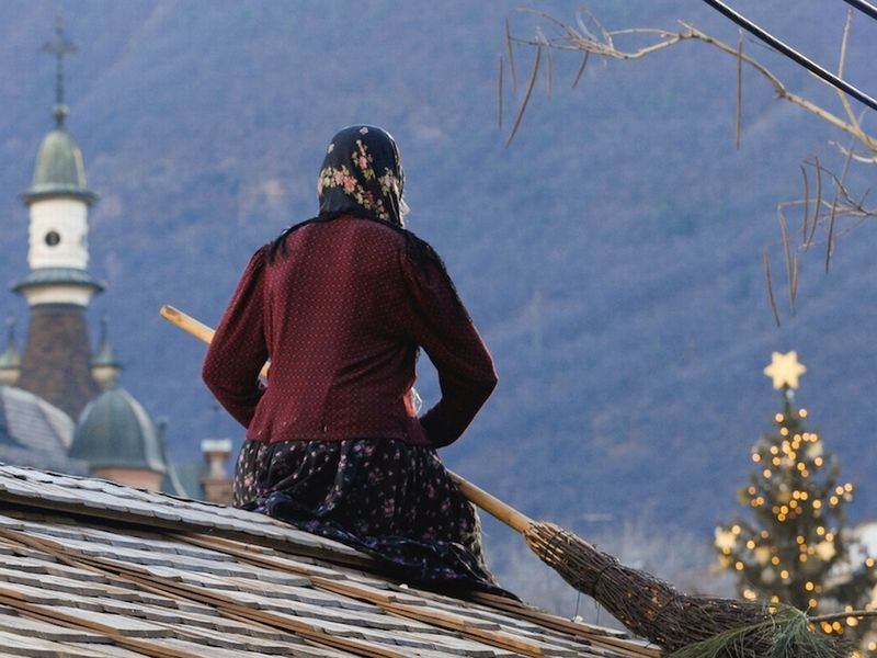 old woman with broom on a roof