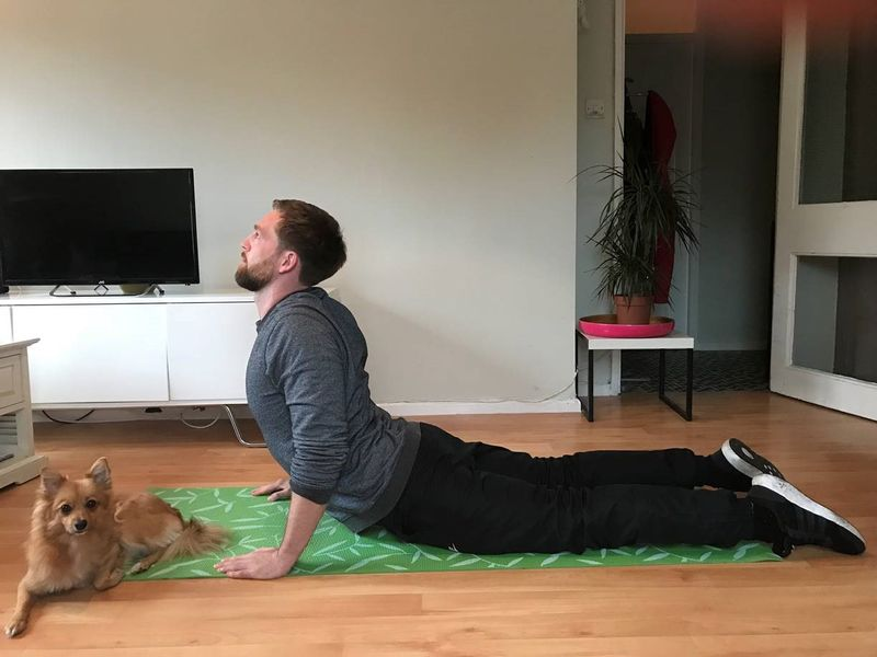man doing yoga with his dog at home