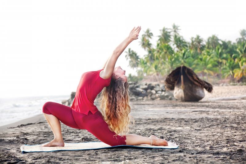 woman in red yoga clothes practicing poses outdoors
