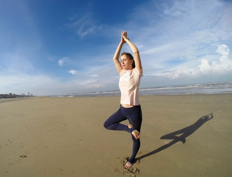 yoga tree pose on the beach