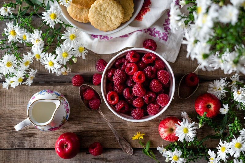 raspberries and chamomile flowers breakfast table