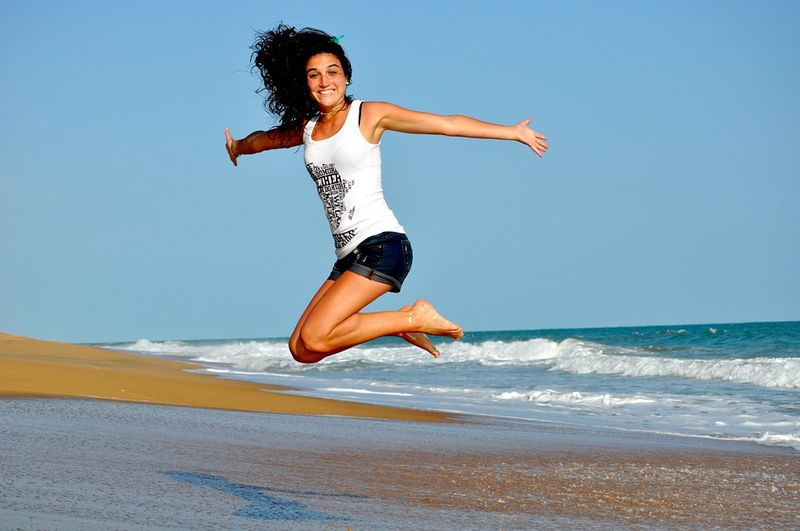 woman on beach high energy jump