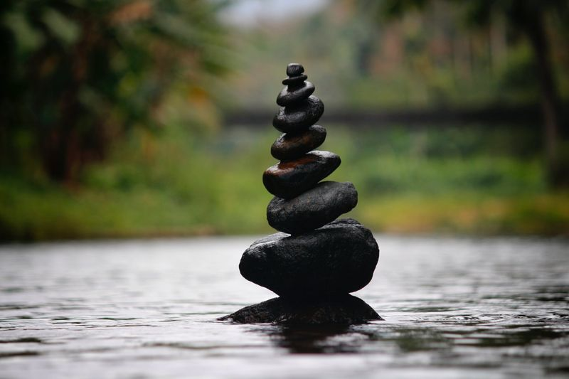 stack of stones in river meditation concept photo