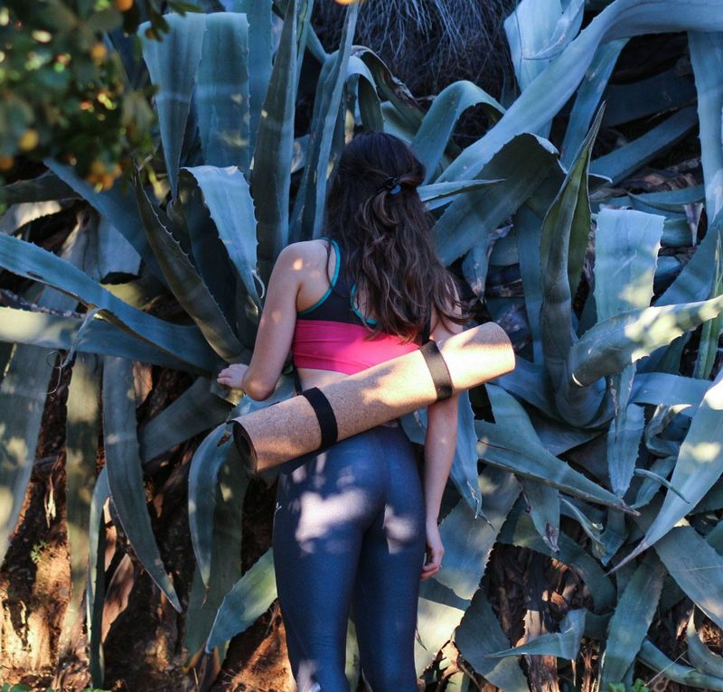 woman with rolled up cork yoga mat carried on her back in the forest