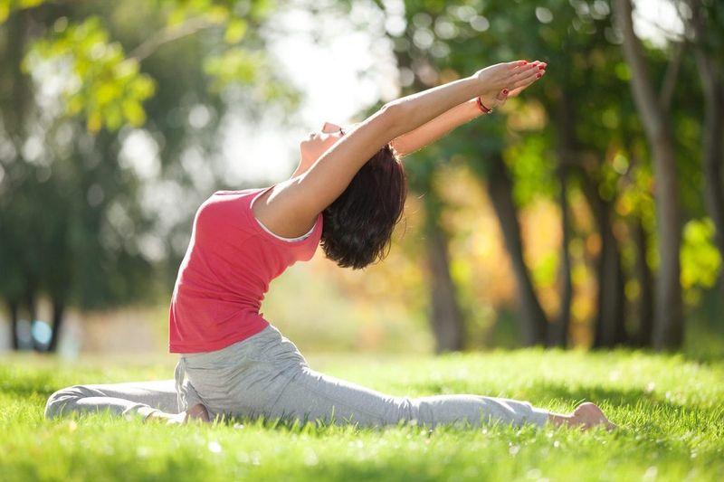 woman doing yoga on grass new york