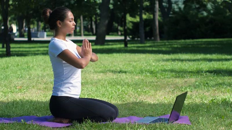 practicing yoga with laptop in nature