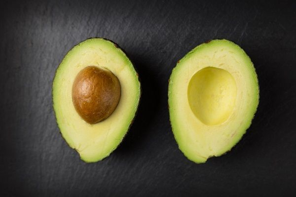 avocados halved on dark grey background