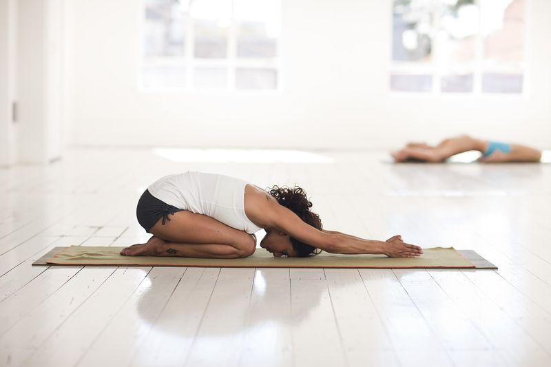 woman in child pose on yoga mat