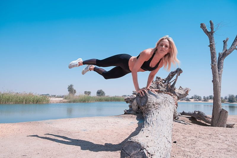 woman balancing herself on her arms on a tree stump