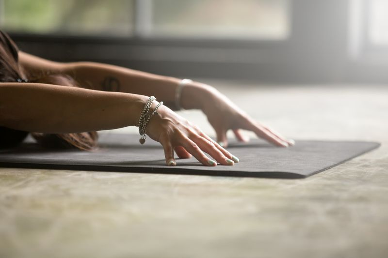 woman practicing yin yoga with hands outstretched