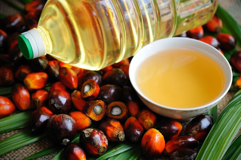 palm oil in a bowl and bottle next to fruit