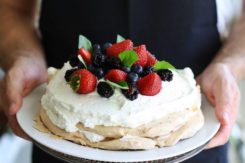 a baker holding pavlova