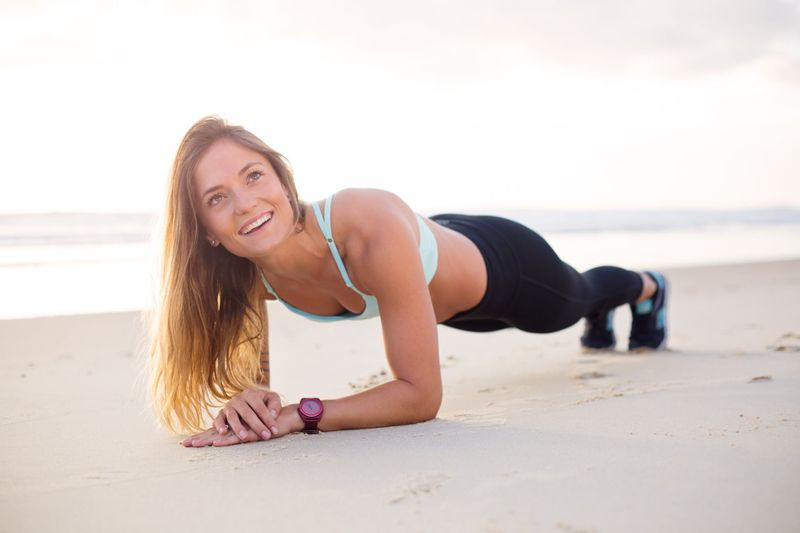 woman doing a warm up on the beach before exercise