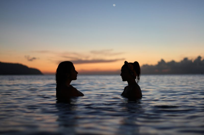 two women silhouettes in water