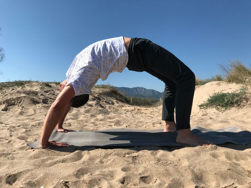 man doing yoga on the beach in valencia spain