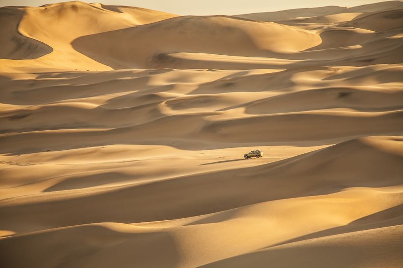car among the dunes in namibia