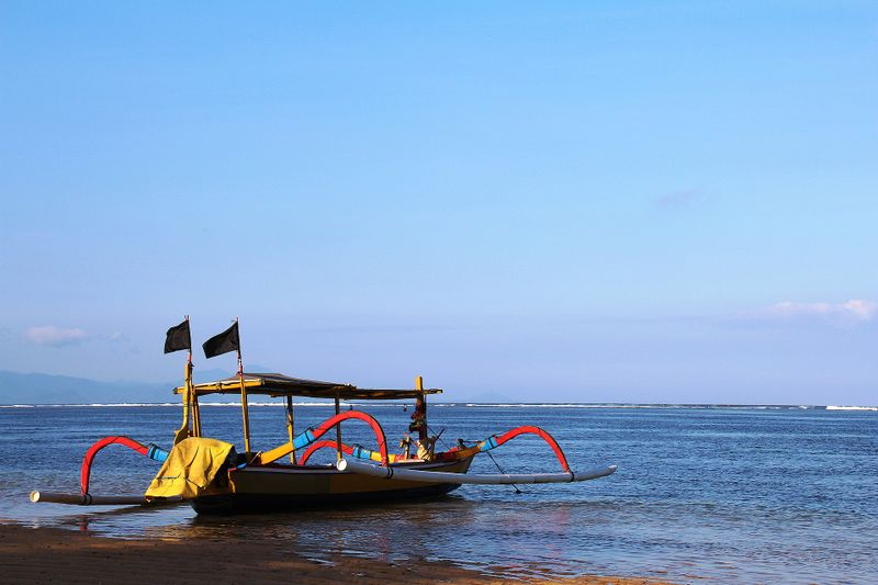 seaside in bali with colorful flags on barge