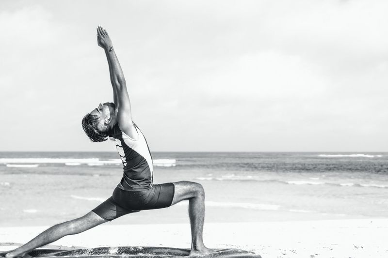 man stretched in yoga pose black and white photo
