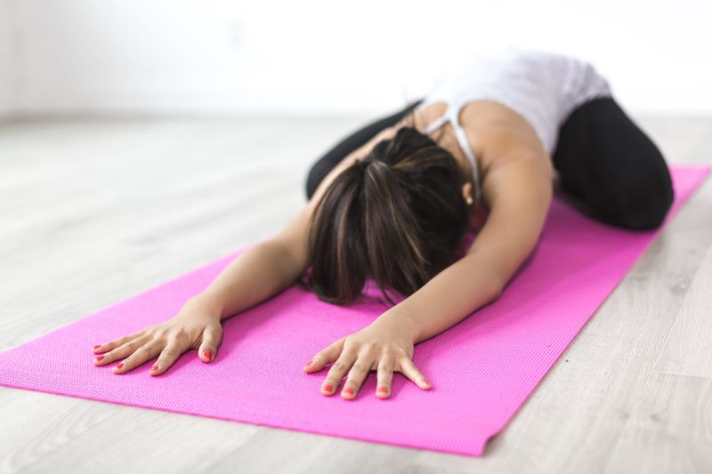 girl strectching with arms out front on a yoga mat