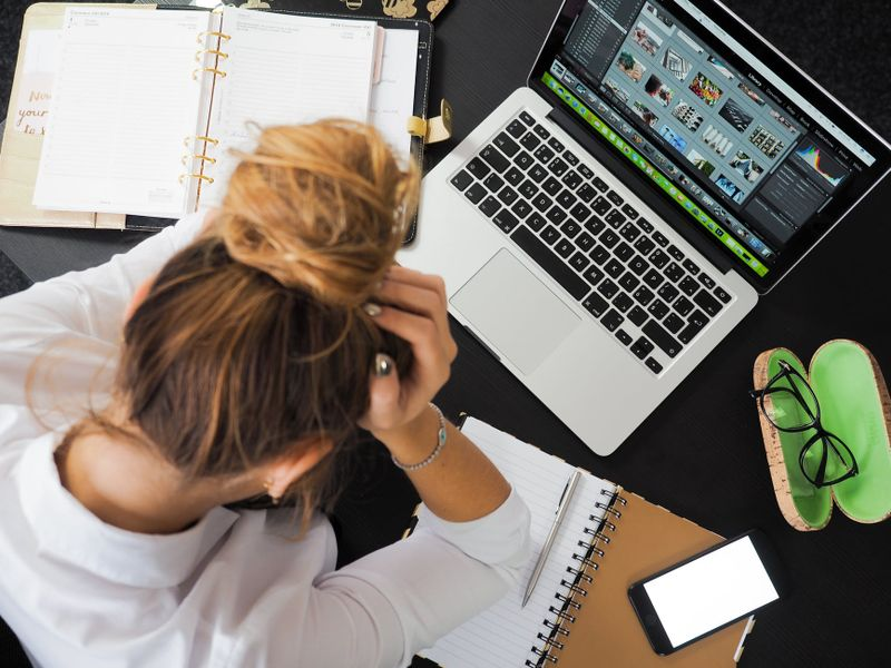 woman feeling stressed in front of laptop