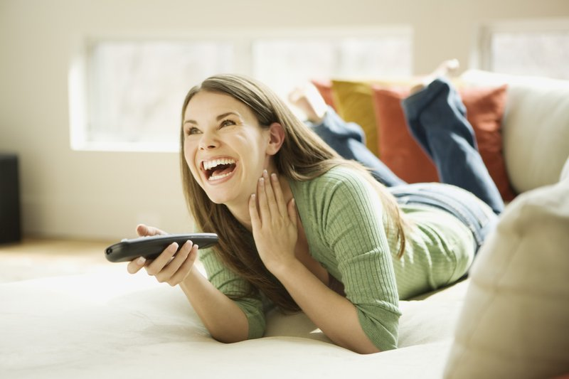 Woman laughing watching TV