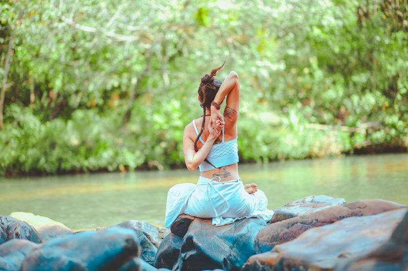 woman striking a yoga pose by the river