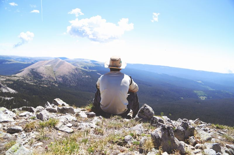 man on a mountaintop overlooking the valley