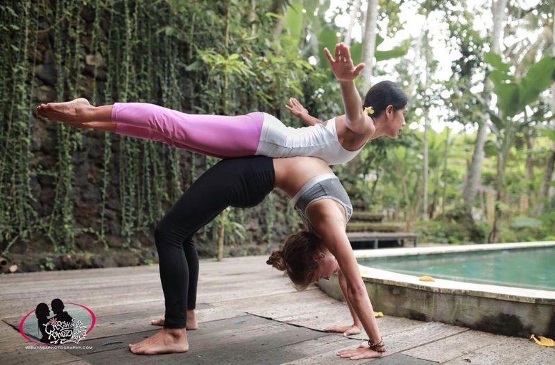 2 yogis doing a partner pose in bali yoga retreat