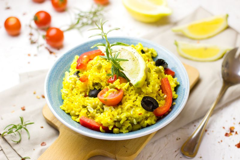 paella dish on white table with cherry tomatoes in background